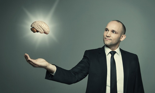 Man with brain model floating above hand