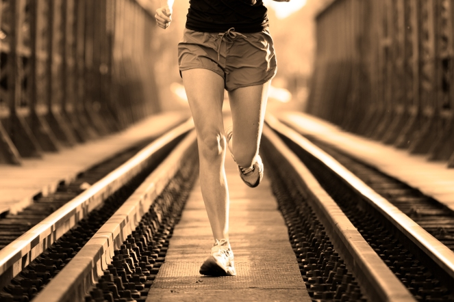 Active female athlete running on railaway tracks.