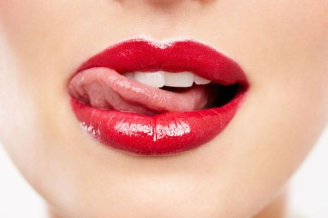 Cropped closeup of a woman wearing red lipstick and licking her lip