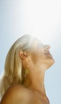Upward view of a smiling woman against the sunny sky